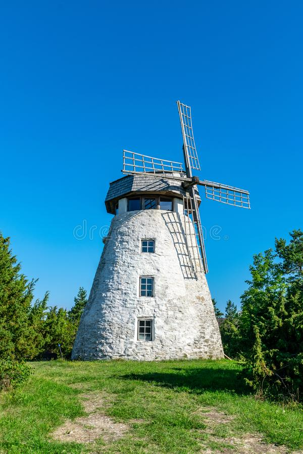 white brick windmill on blue sky background royalty free stock photo