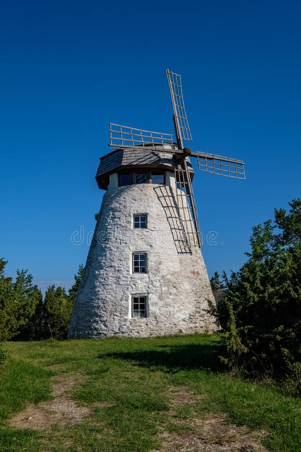 white brick windmill on blue sky background stock images