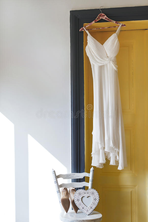 White bridal dress hanging on peg. Near door. Shoes and white heart lying on chair. No people, indoor, interior, studio royalty free stock photo