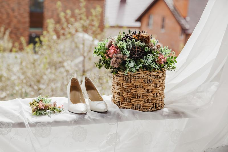 white bridal shoes and flowers in the basket stock photo