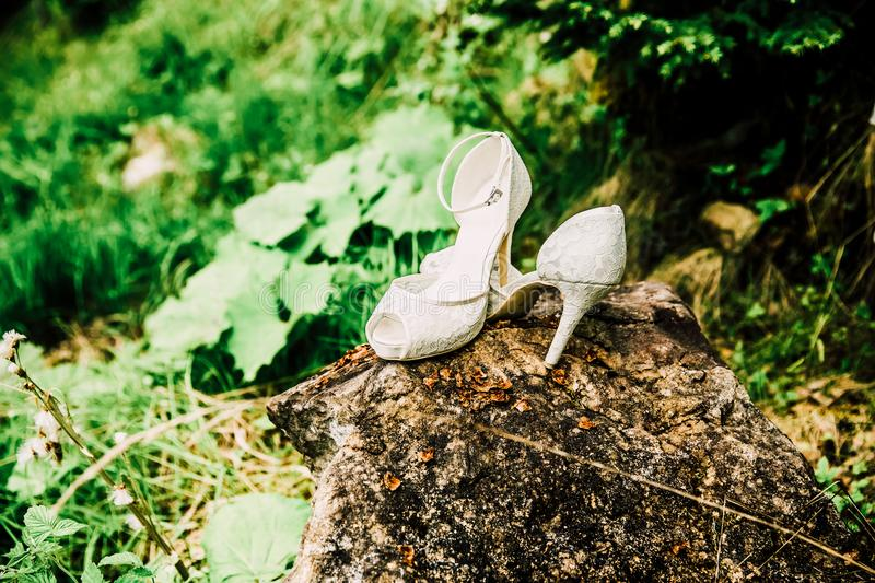 White Bridal Wedding Shoes on a Rock in a Forest. White Bridal Wedding Shoes on a Rock in Green Forest in Summer stock photography