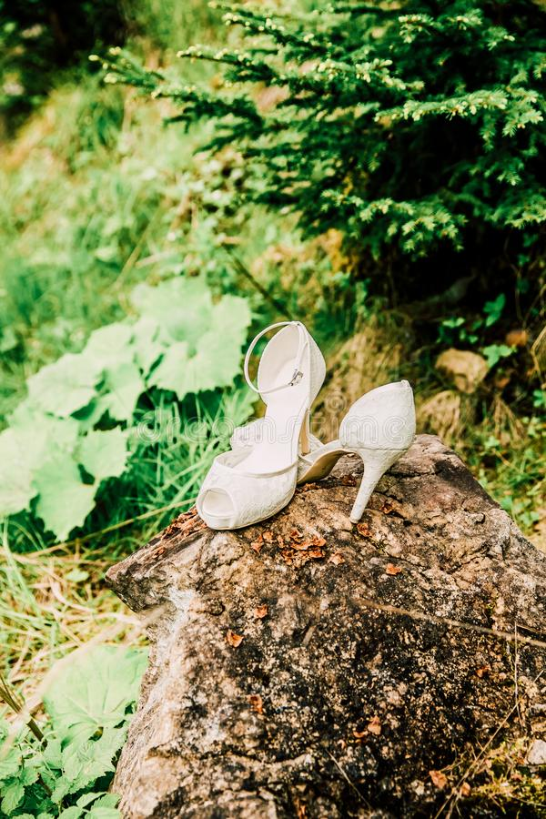 White Bridal Wedding Shoes on a Rock in Green Forest. In Summer stock images