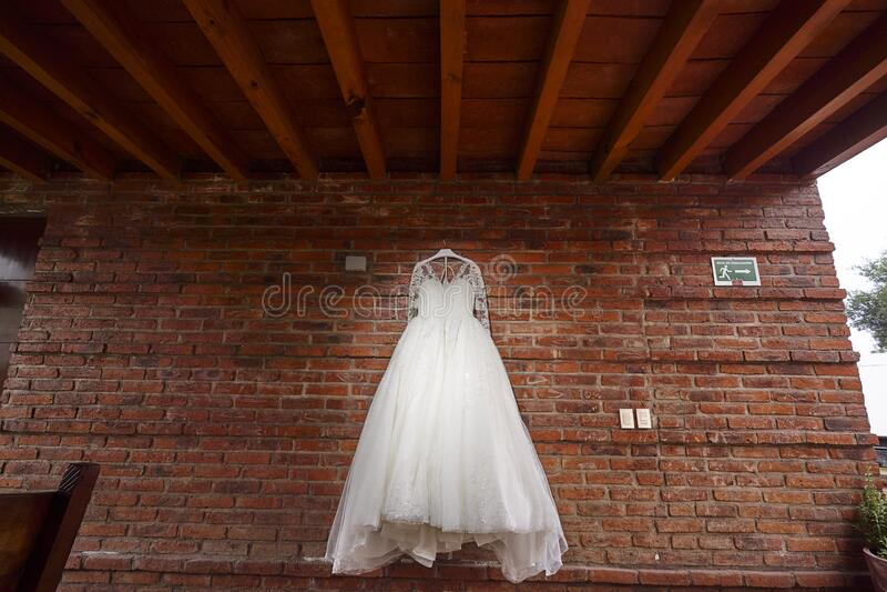 White bride dress hanging in red brick wall colonial hacienda, rustic weddings. White luxury bride dress hanging in red brick wall colonial hacienda, rustic stock photo