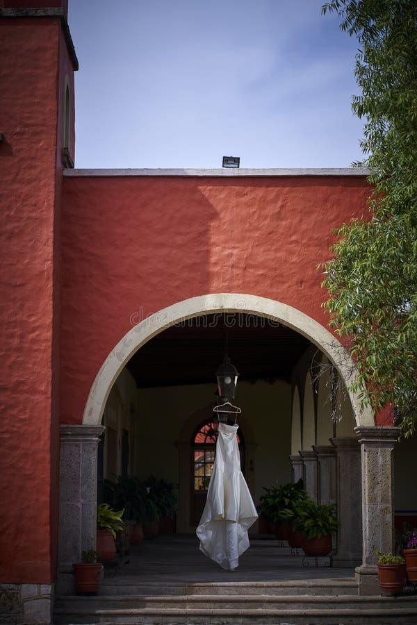 White bride dress hanging in red colonial hacienda, rustic weddings. White luxury bride dress hanging in colonial hacienda, rustic weddings royalty free stock photos
