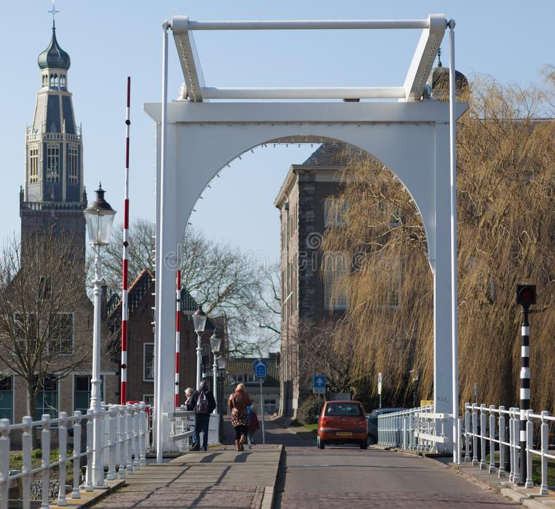 White bridge in fishing village Huizen in the Netherlands. In the background the town hall and willow in spring on a sunny day royalty free stock photos