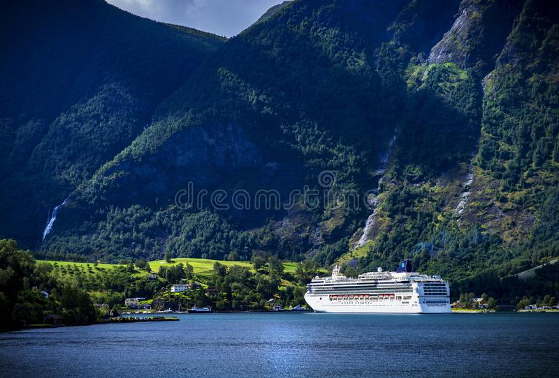 A white bright cruise-ship arrives at a fjord village in norway. royalty free stock photos