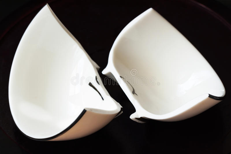 White broken cup and fractured shards of glass. View of a white broken cup and fractured shards of sharp glass fragments scattered on black background. Concept royalty free stock photos