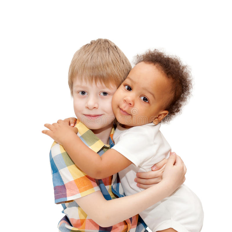 White brother hugging black baby sister. Multiracial happy family. White brother hugging black baby sister royalty free stock photo