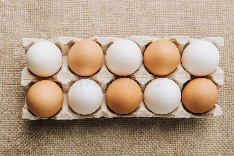 White and brown eggs laying in egg carton. On sackcloth royalty free stock image