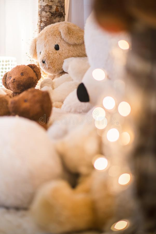 White and brown teddy bears closeup lay indoor with christmast light halos in the foreground royalty free stock photos
