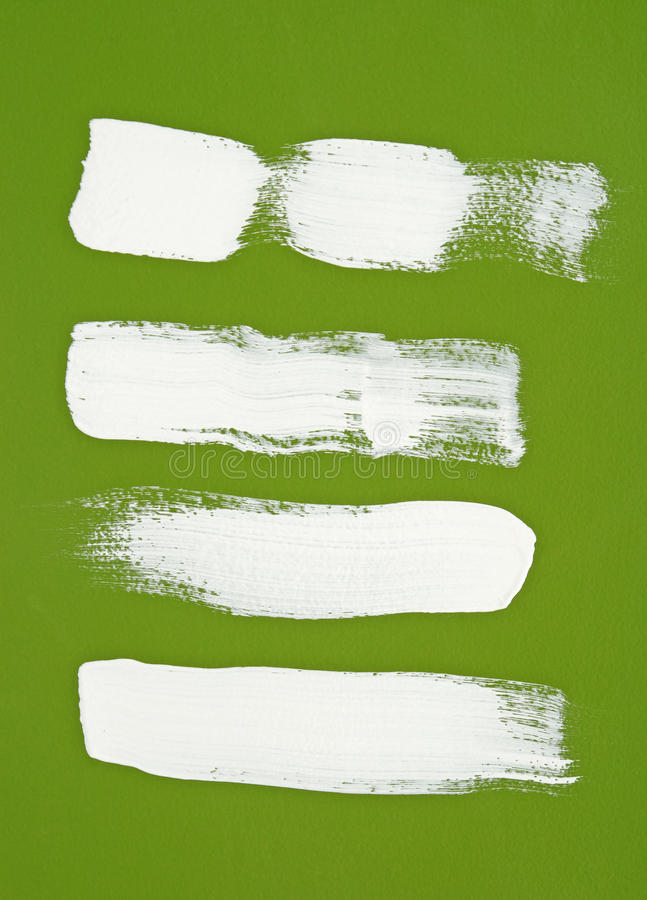 White brush strokes on green background. White brush strokes on bright green background royalty free stock photo