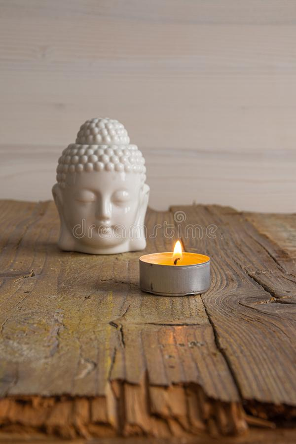 White buddha figure and candle. On weathered wooden board royalty free stock image