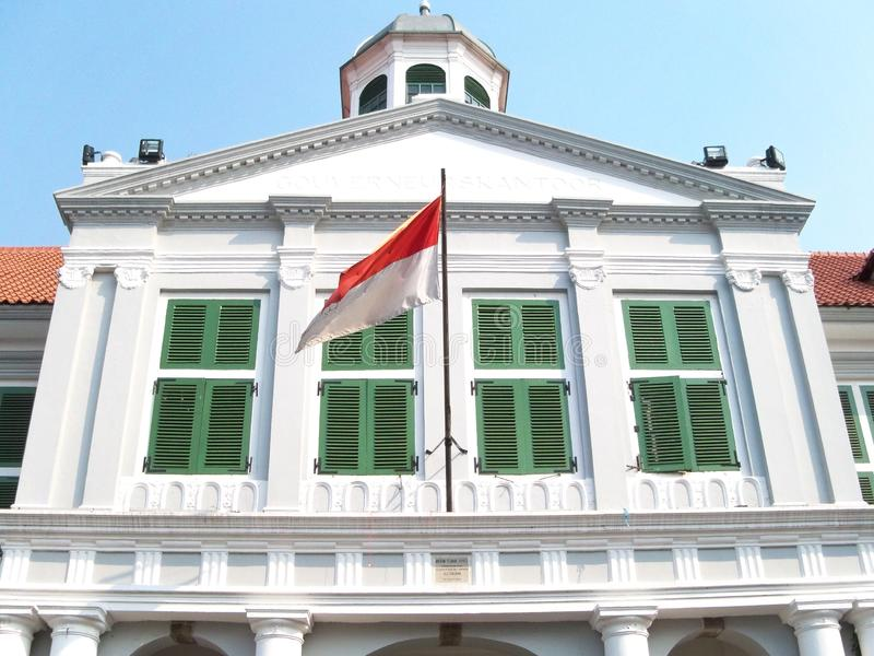 White building with Indonesia flag in front of it royalty free stock photography