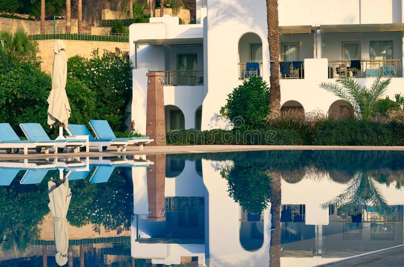 White building with pool and palm trees.  stock photo
