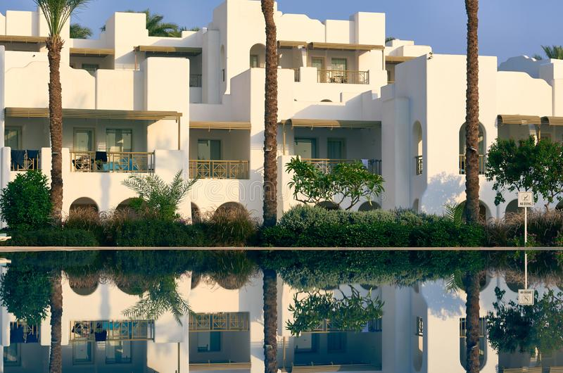White building with pool and palm trees.  royalty free stock photos