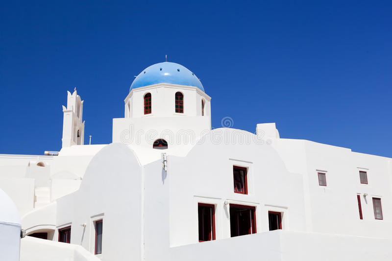 White buildings and church with blue dome in Oia or Ia on Santorini island, Greece stock image