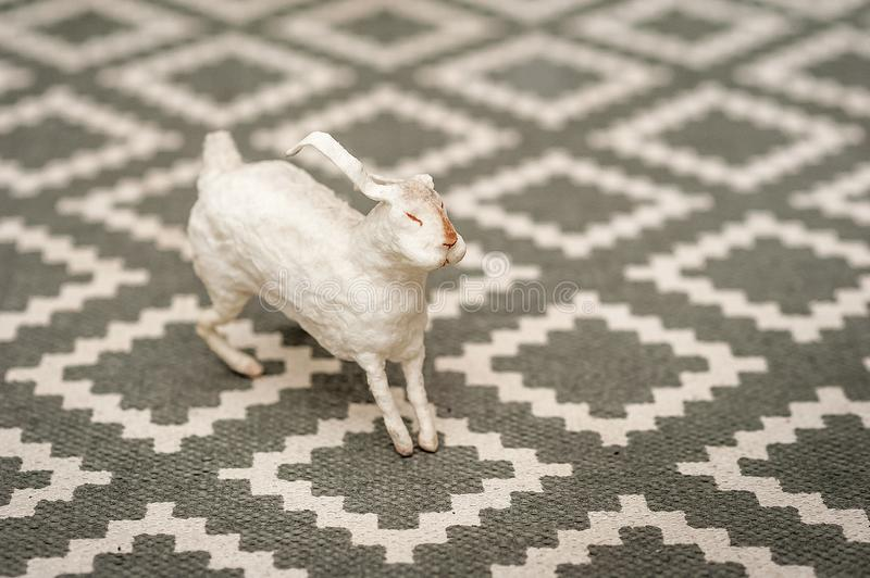 White bunny on a textural background of a carpet with a geometric pattern. Easter concept, tenderness, uniqueness, beauty. Bunny c. Lose up and copy space stock photography