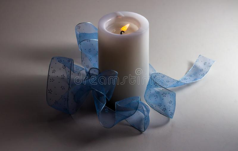 A white burning candle is on a white background and decorated with a light blue ribbon stock photos