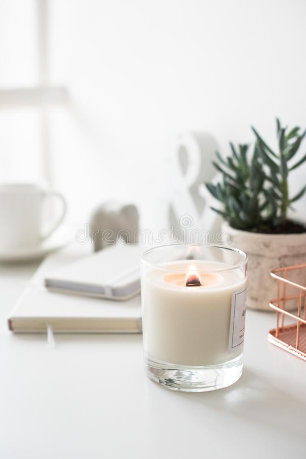 White burning candle on table, home interior decorations stock image