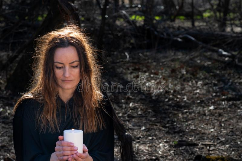 White burning Candle in woman`s hands in the middle of the forest. Hope and Pray concept. All Saints Day celebration. Witchcraft royalty free stock photography
