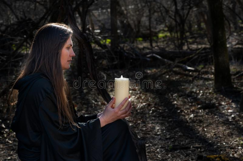 White burning Candle in woman`s hands in the middle of the forest. Hope and Pray concept. All Saints Day celebration. Witchcraft stock image