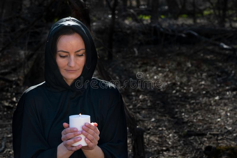White burning Candle in woman`s hands in the middle of the forest. Hope and Pray concept. All Saints Day celebration. Witchcraft stock photos