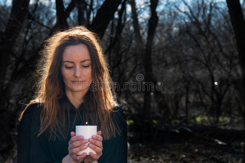 White burning Candle in woman`s hands in the middle of the forest. Hope and Pray concept. All Saints Day celebration. Witchcraft stock photo