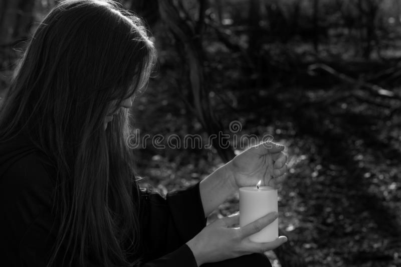 White burning Candle in woman`s hands in the middle of the forest. Hope and Pray concept. All Saints Day celebration. Witchcraft royalty free stock photos
