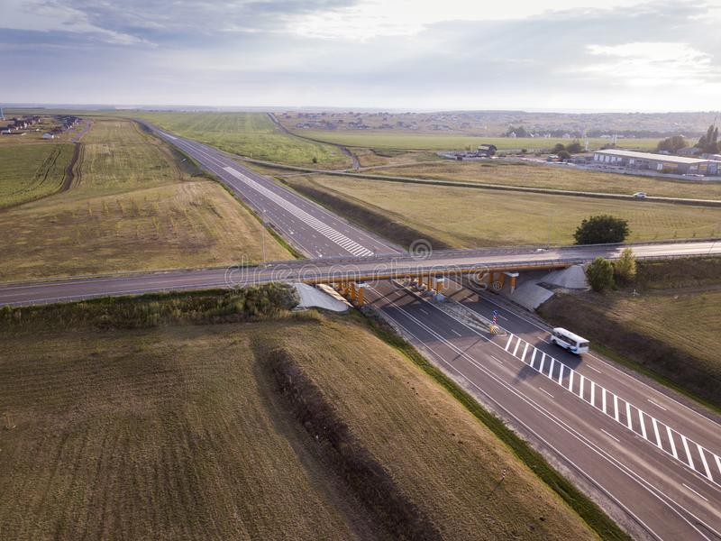 White Bus Passing Highway Overpass. Car on road. Aerial View royalty free stock photo