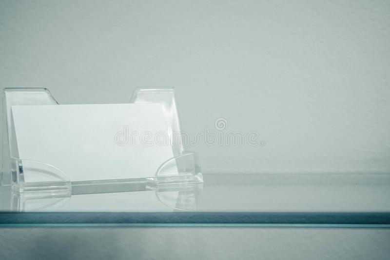 Acrylic paper stand for a blank card, business card stand on glass shelf . Flyer leaflet white paper card template design. stock photos