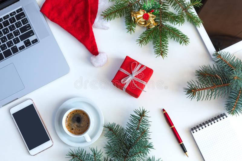 White Business Table top View Christmas Theme Items. Top View of white Office Table with cropped Laptop and Christmas Theme Items Tree Santa Cap Notepad royalty free stock photography