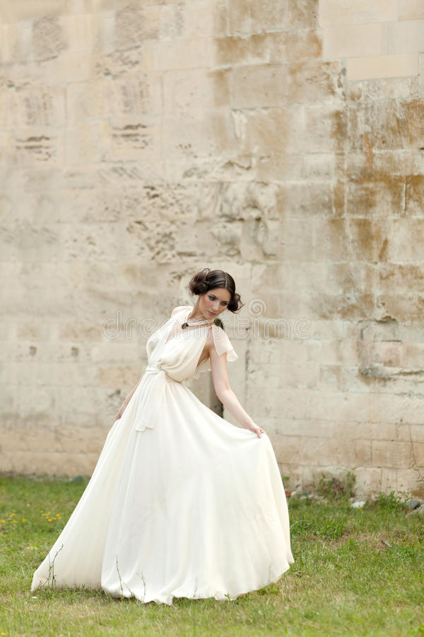 White Butterfly Woman. Beautiful ellegant woman in white long dress, elegantly holding its fold, having a graceful attitude as id dancing stock photo