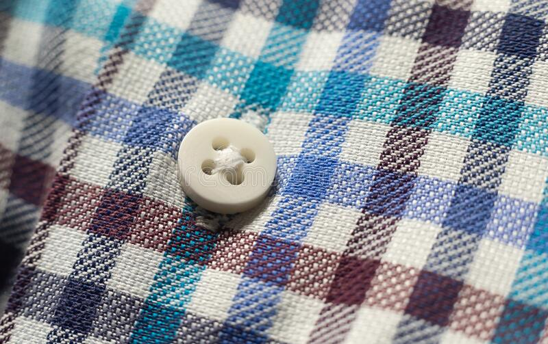 White button on adhesive fabric of multicolored shirt.  royalty free stock photography