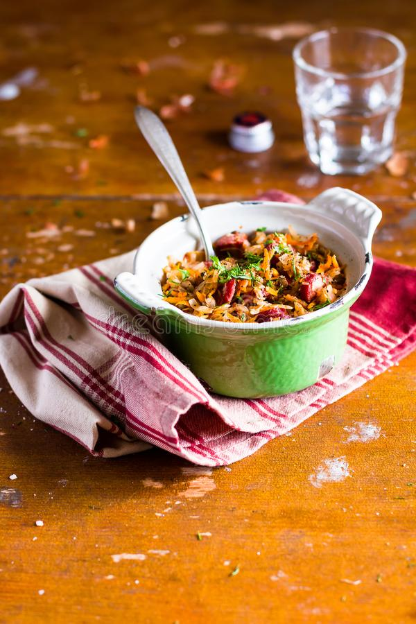 White cabbage stew with green lentil and sausages in a pot on a wooden table, selective focus royalty free stock image