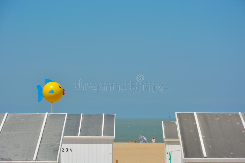 White cabinets a funny yellow fish and unidentifiable people sunbathing on a summer-beach royalty free stock images