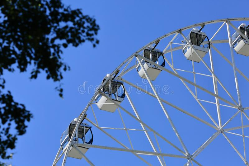 The white cabins of the Ferris wheel on blue sky background royalty free stock image