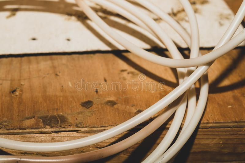White cable lies on the wooden table. connection wire. Close up, electric, copper, background, power, color, energy, line, plastic, electronic, underground stock image