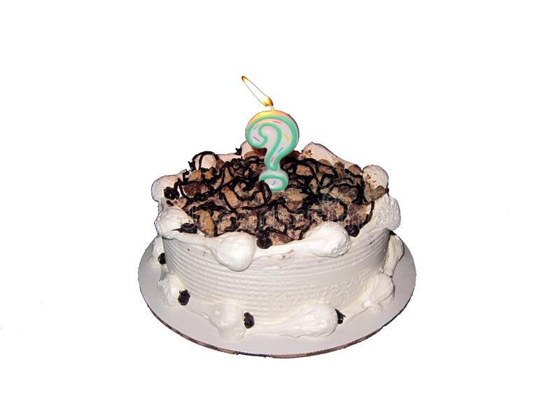 White cake with chocolate syrup and a question mark candle on a white background. A white cake with chocolate syrup and a question mark candle on a white stock photos