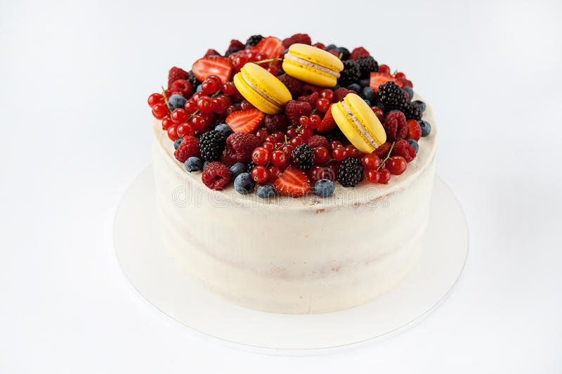 White cake with fruits and makarons. Beautiful white cake with fruits and makarons stock photo