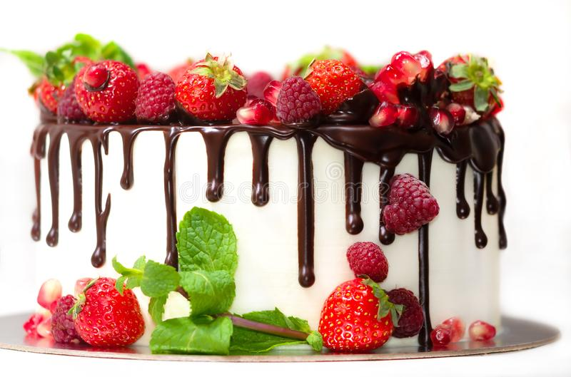 White cake poured with brown chocolate and decorated with berries on an isolated white background. White cake poured with brown chocolate and decorated with royalty free stock image
