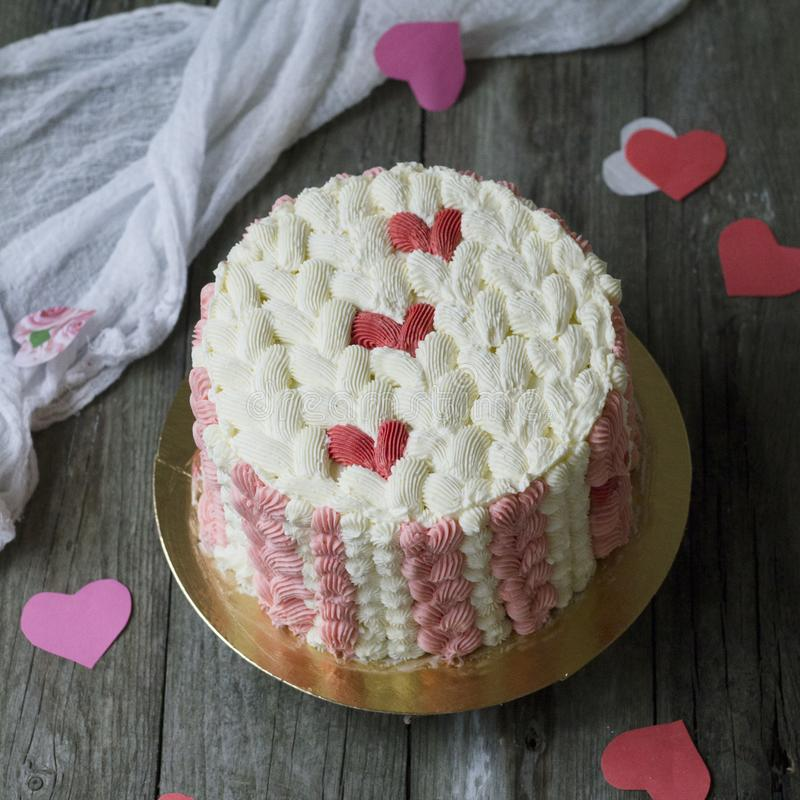 White cake with red cream heart on wooden background with lace fabric. The effect of a knitted surface on the cake. Valentines Day stock images