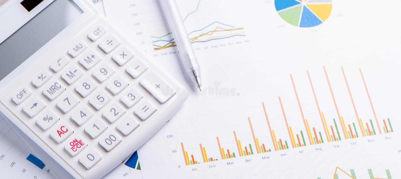 White calculator and report with chart and graph, concept of annual financial profit overview, banking and investment, close up,. Copy space, macro royalty free stock image