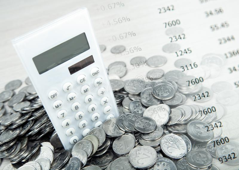 White calculator with russian ruble coins and digits. Close up stock photography