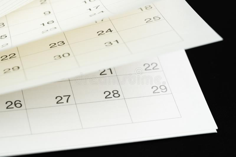 White calendar turning pages with dark black background using as time fly, season pass or reminder and appointment is coming. Concept royalty free stock image
