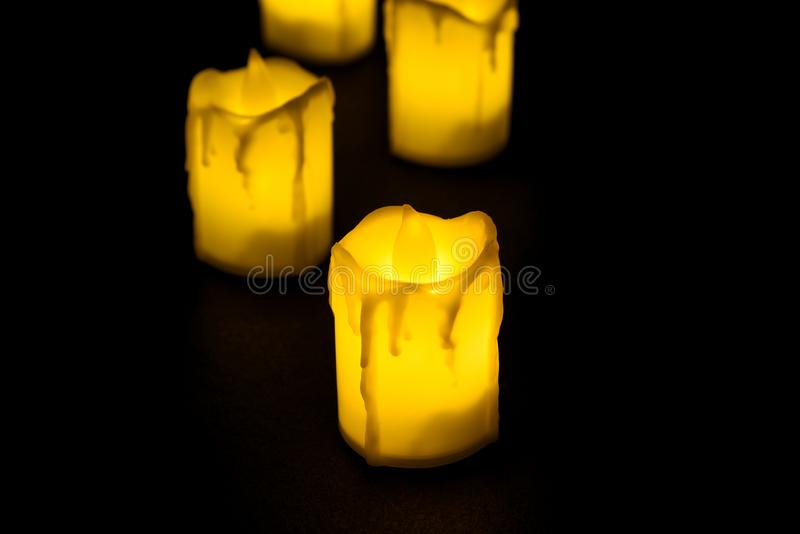 White candle on black background isolated. Set of  candle.Small candle with light yellow spots on light background. Christmas. Decor stock images