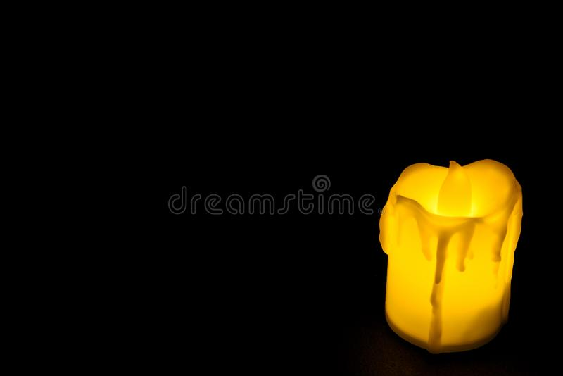 White candle on black background isolated. Small candle with light yellow spots on light background. Christmas decor.  stock images