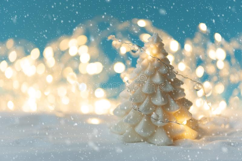 White candle on Christmas fir tree shape on snowy and defocused lights background. Christmas or New Year celebration concept. Copy stock photo