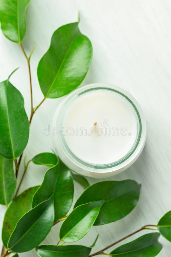 White Candle in Glass Jar Fresh Tree Branches with Tender Green Leaves on Wood Background. Spa Wellness Body Care Meditation. Concept. Minimalist Scandinavian stock images