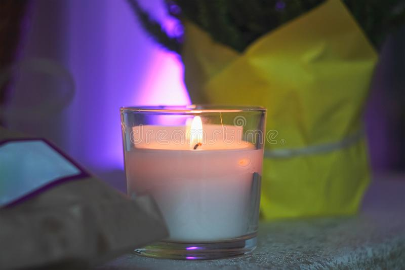 white candle in a glass on a table stock photo