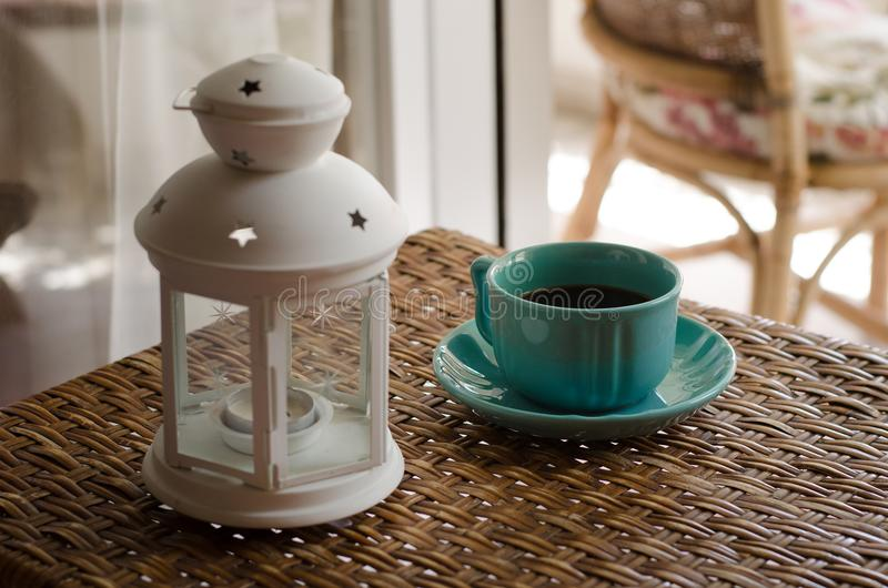White Candle Lantern Beside of Blue Ceramic Coffee Mug on Wicker Table stock image